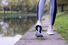 Funzionamento sportivo della donna sulla sponda del fiume Concetto di benessere di allenamento e di forma fisica Fotografie Stock