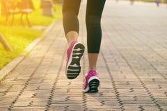 Funzionamento sportivo della donna sulla strada ad alba Fotografie Stock Libere da Diritti