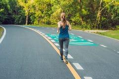 Funzionamento sportivo della donna sulla strada ad alba Concetto di benessere di allenamento e di forma fisica Immagine Stock