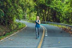 Funzionamento sportivo della donna sulla strada ad alba Concetto di benessere di allenamento e di forma fisica Immagini Stock