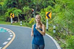 Funzionamento sportivo della donna sulla strada ad alba Concetto di benessere di allenamento e di forma fisica Fotografia Stock