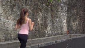 Funzionamento sportivo della donna sulla strada ad alba Concetto di benessere e di forma fisica stock footage