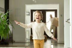 Funzionamento sveglio del ragazzo del bambino che esplora nuovo trasloco con i genitori immagini stock