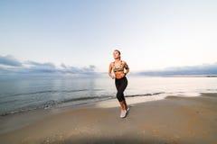 Funzionamento sveglio della ragazza di misura sulla spiaggia ad alba Fotografia Stock Libera da Diritti