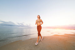 Funzionamento sveglio della ragazza di misura sulla spiaggia ad alba Immagini Stock