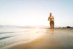 Funzionamento sveglio della ragazza di misura sulla spiaggia ad alba Fotografie Stock Libere da Diritti
