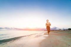 Funzionamento sveglio della ragazza di misura sulla spiaggia ad alba Fotografie Stock