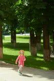 Funzionamento sveglio felice della bambina nel parco felicità Fotografie Stock Libere da Diritti
