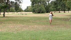 Funzionamento teenager caucasico della donna nel parco Grey Dress And Sandals video d archivio