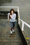 Funzionamento urbano della donna di forma fisica e scale rampicanti Fotografia Stock