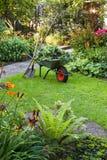 Funzionando con la carriola nel giardino Immagine Stock