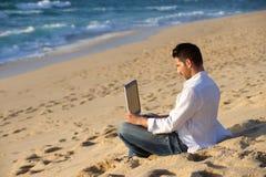 Funzionando nel computer portatile alla spiaggia Fotografia Stock