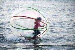 Funzionando su una ragazza delle onde all'interno della sfera di plastica Fotografie Stock Libere da Diritti