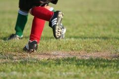 Funzionando sul campo di calcio Fotografie Stock Libere da Diritti
