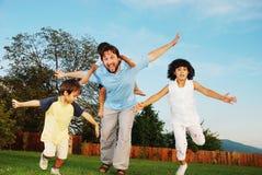 Funzionare felice della famiglia esterno sul bello giardino fotografia stock libera da diritti