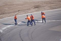 Funzionari della corsa che puliscono pista Fotografie Stock Libere da Diritti