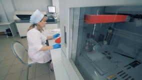 Funzione del laboratorio con un analizzatore biochimico e uno specialista di signora archivi video