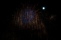 Fuochi d'artificio blu e rossi al fondo di notte con la luna Fotografie Stock