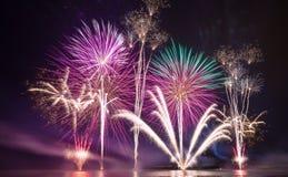 Fuochi d'artificio brillantemente variopinti sparati sopra il mare Immagine Stock Libera da Diritti