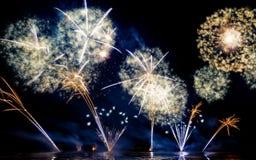 Fuochi d'artificio brillantemente variopinti sparati sopra il mare Immagini Stock Libere da Diritti