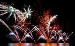 Fuochi d'artificio brillantemente variopinti sparati sopra il mare Immagine Stock