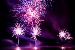 Fuochi d'artificio brillantemente variopinti sparati sopra il mare Fotografia Stock