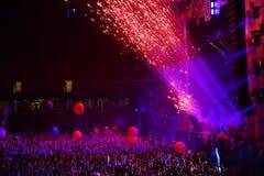 Fuochi d'artificio che fanno fuoco nella parte anteriore della folla contro un concerto in tensione Immagine Stock Libera da Diritti