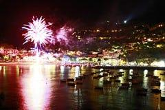 Fuochi d'artificio di notte di metà dell'estate dal mare immagini stock
