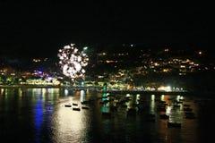 Fuochi d'artificio di notte di metà dell'estate dal mare fotografia stock