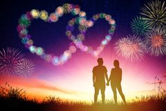 fuochi d'artificio di sorveglianza di forma del cuore delle coppie sulla collina immagine stock libera da diritti