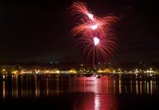 Fuochi d'artificio Fuochi d'artificio stupefacenti differenti variopinti con la luna, i precedenti scuri del cielo e la luce di s Immagini Stock