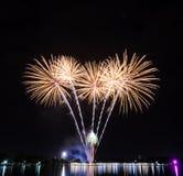 Fuochi d'artificio gialli con le luci di riflessione sul lago Immagine Stock