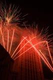 Fuochi d'artificio rossi intorno ad un edificio alto Fotografie Stock