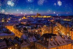 Fuochi d'artificio sopra il castello di Praga con i tetti nevosi durante il tramonto recente di natale Fotografia Stock