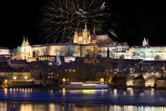 Fuochi d'artificio sopra il castello gotico nevoso variopinto di Praga di notte con Charles Bridge, repubblica Ceca Fotografie Stock Libere da Diritti