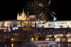 Fuochi d'artificio sopra il castello gotico nevoso variopinto di Praga di notte con Charles Bridge, repubblica Ceca Fotografia Stock