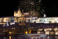 Fuochi d'artificio sopra il castello gotico nevoso variopinto di Praga di notte con Charles Bridge, repubblica Ceca Immagine Stock Libera da Diritti