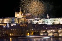 Fuochi d'artificio sopra il castello gotico nevoso variopinto di Praga di notte con Charles Bridge, repubblica Ceca Immagini Stock Libere da Diritti