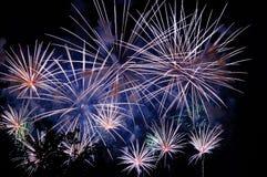 Fuochi d'artificio stupefacenti blu e dorati bianchi su fondo scuro Fotografia Stock