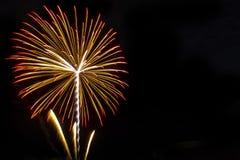 Fuochi d'artificio sui precedenti neri del cielo con la riflessione su acqua a fotografia stock