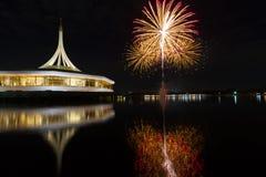 Fuochi d'artificio sui precedenti neri del cielo con la riflessione su acqua a fotografia stock libera da diritti