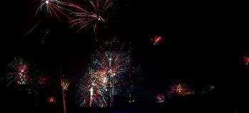 Fuochi d'artificio variopinti del ` s EVE del nuovo anno sopra il cielo della città Immagini Stock