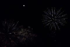 Fuochi d'artificio variopinti e stelle filante bianche sotto una luna piena luminosa Fotografia Stock