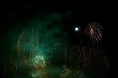 Fuochi d'artificio verdi e dorati al fondo di notte con la luna Immagini Stock