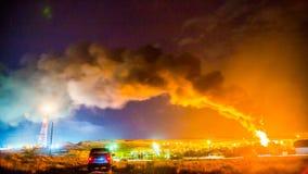Fuoco ad una raffineria di petrolio, alla notte durante il temporale stock footage
