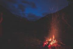 Fuoco bruciante del campo nel terreno boscoso a distanza del pino e del larice con il paesaggio di elevata altitudine ed il cielo Immagini Stock