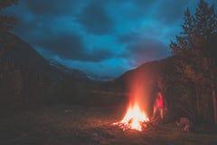 Fuoco bruciante del campo nel terreno boscoso a distanza del pino e del larice con il paesaggio di elevata altitudine ed il cielo Immagine Stock