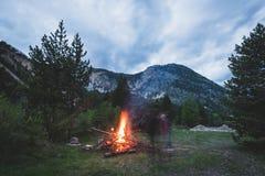 Fuoco bruciante del campo nel terreno boscoso a distanza del pino e del larice con il paesaggio di elevata altitudine ed il cielo Fotografia Stock
