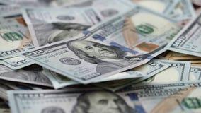 Fuoco che si muove lungo la banconota in dollari degli Stati Uniti cento in mucchio di soldi enorme video d archivio