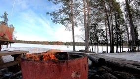 Fuoco con legno per il barbecue in una terra della neve coperta di alberi e di lago congelato dietro di bello paesaggio in un nuv stock footage